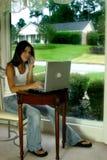 Vrouw op telefoon met laptop Stock Afbeeldingen