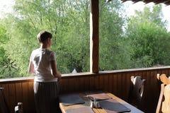 Vrouw op terras in koffie Stock Foto