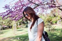 Vrouw op verbazende bloeiende boomachtergrond Modieuze rugzak, de lentekleuren, donkerbruin meisje in een park, het rusten, wit o Stock Foto