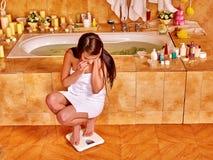 Vrouw op vloerschalen die wordt gewogen Stock Foto