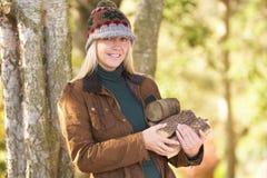 Vrouw in openlucht in het Bos dat van de Herfst Logboeken verzamelt Royalty-vrije Stock Afbeelding