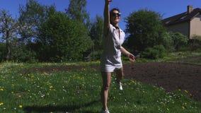 Vrouw openlucht werpend een vliegende schijf stock footage