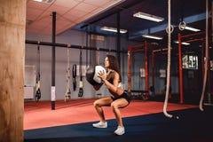 Vrouw opleiding met functionele gymnastiek- in de gymnastiek Royalty-vrije Stock Afbeeldingen