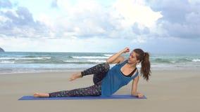 Vrouw opleiding op het strand dichtbij overzees Gymnastiek- ochtend Zijplankoefening stock videobeelden