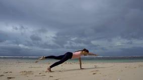 Vrouw opleiding op het strand voor overzees Één hand één de oefening van de beenplank stock videobeelden