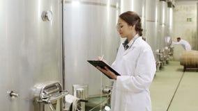 Vrouw opstijgen eenvormig met materiaal, brouwerijgisting stock videobeelden