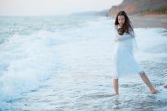 Vrouw in overzeese golven bij zonsondergang Royalty-vrije Stock Afbeeldingen