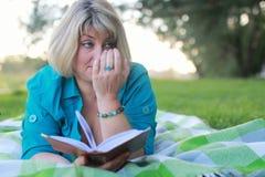 Vrouw in park met boek op gras Stock Afbeeldingen