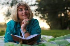 Vrouw in park met boek op het gras Royalty-vrije Stock Foto