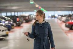 Vrouw in parkerengarage met sleutel Stock Afbeeldingen