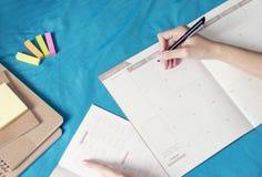 Vrouw planningsagenda en programma die de ontwerper van de kalendergebeurtenis, gebruiken die plan op memorandumprogramma schrijv stock fotografie
