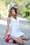 Vrouw in plotseling witte kleding en rode hoge hielen stock foto's