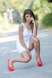 Vrouw in plotseling witte kleding en rode hoge hielen stock afbeeldingen