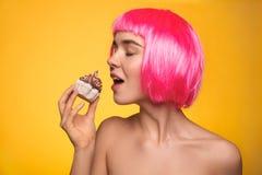 Vrouw in pruik die cupcake bijten Royalty-vrije Stock Afbeelding