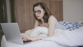 Vrouw in pyjama's die laptop met behulp van stock footage