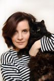 Vrouw r met een zwarte kat in haar wapens Stock Afbeeldingen