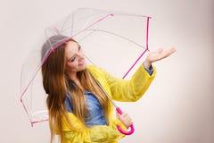 Vrouw in regendichte laag met paraplu forecasting stock afbeelding
