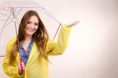 Vrouw in regendichte laag met paraplu forecasting stock fotografie