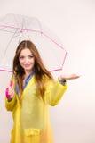 Vrouw in regendichte laag met paraplu forecasting royalty-vrije stock foto