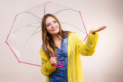 Vrouw in regendichte laag met paraplu forecasting royalty-vrije stock fotografie