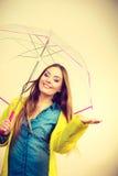 Vrouw in regendichte laag met paraplu forecasting stock foto