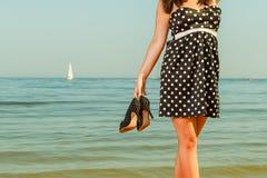 Vrouw in retro schoenen van de kledingsholding dichtbij overzees Royalty-vrije Stock Fotografie