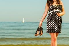Vrouw in retro schoenen van de kledingsholding dichtbij overzees Royalty-vrije Stock Foto's