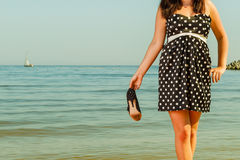 Vrouw in retro schoenen van de kledingsholding dichtbij overzees Royalty-vrije Stock Afbeelding