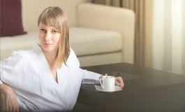 Vrouw in robe met koffie in hotelruimte. Stock Fotografie