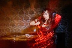 Vrouw in rode golvende kleding in binnenland Stock Afbeeldingen