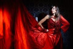 Vrouw in rode golvende kleding in binnenland Royalty-vrije Stock Foto's