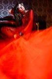 Vrouw in rode golvende kleding in binnenland Stock Foto