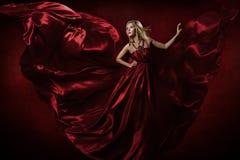 Vrouw in rode golvende kleding die met vliegende stof dansen royalty-vrije stock afbeeldingen