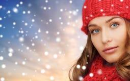 Vrouw in rode hoed en sjaal over sneeuwachtergrond royalty-vrije stock foto's