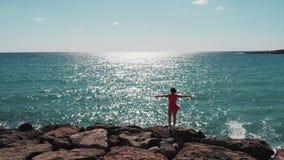 Vrouw in rode kleding met handen apart in lucht die zich op rotsachtig klippenstrand bevinden met hommel die rond haar vliegen Sa stock videobeelden
