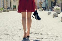 Vrouw in rode kleding, met hoge in hand hielschoenen, lopend in royalty-vrije stock foto's