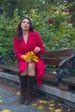 Vrouw in rode laag op de bank in de herfstpark Stock Foto's