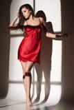 Vrouw in rode nachtjapon gezien venster Stock Afbeelding