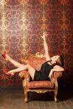 Vrouw in rode schoenen en kledingszitting op stoel Royalty-vrije Stock Afbeeldingen