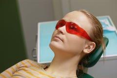 Vrouw in rode veiligheidsbril in tandbureau stock foto's