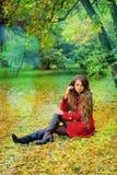 Vrouw in rode zitting in de herfstpark Royalty-vrije Stock Foto's