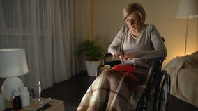 Vrouw in rolstoel die aan parkinsonian trilling, hulpeloosheid in oude dag lijden stock videobeelden