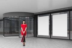 Vrouw in rood dichtbij een wandelgalerij royalty-vrije stock afbeelding