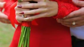 Vrouw in rood die een boeket van bloemen houden stock video