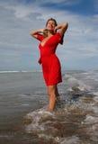 Vrouw in rood in ondiepe bekers onder blauwe hemel Stock Foto