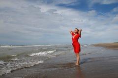 Vrouw in rood op oceanic kust onder blauwe hemel Stock Afbeeldingen