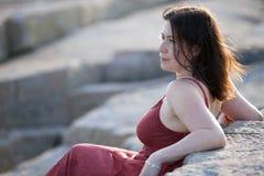 Vrouw in rood op rotsachtig strand bij zonsondergang 1 Stock Afbeeldingen