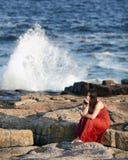Vrouw in rood op rotsachtig strand bij zonsondergang 2 Royalty-vrije Stock Foto's