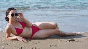 Vrouw in rood zwempak die op het strand en het zonnebaden liggen stock footage