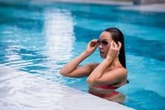 Vrouw rood zwempak dragen en zonnebril die in zwembad, wat betreft nat haar zitten Royalty-vrije Stock Fotografie